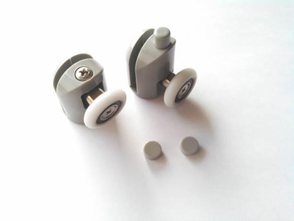 Petite roue blanche de diamètre 20 à 25 millimètres et épaisse de environ 5 millimètres, un roulement à billes est au centre de cette roue qui sert à faire coulisser une porte