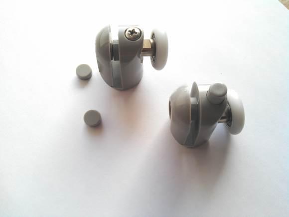 Cette roulette est une bague blanche en plastique de diamètre 20 à 25 millimètres et d'une épaisseur de environ 5 millimètres, elle sert à faire coulisser une porte